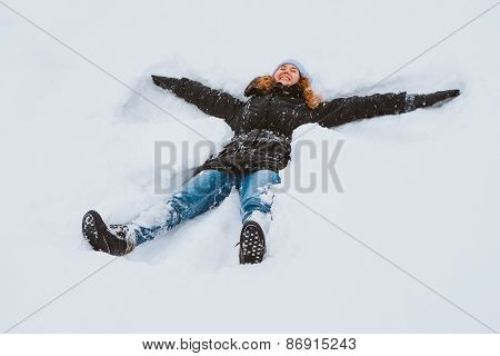 Portrait Of A Beautiful Young Woman Laying Down On A Frozen Snow Lake Moving Her Arms And Legs Up An