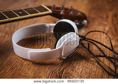 Acoustic Guitar And Headphone On Fabric Sofa