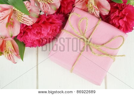 Pink gift box with flowers on white wood
