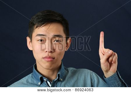Funny young Asian man pointing his index finger upward and looking at camera