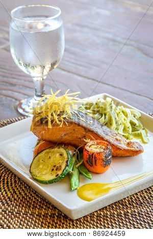 grilled salmon steak served with pasta and vegetables in a small outdoor restaurant