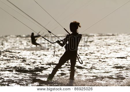 silhouette of female kite surfer in water