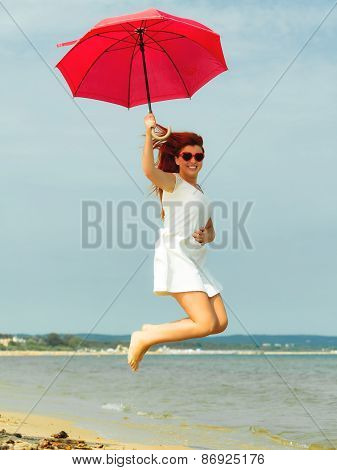 Redhaired Girl Jumping With Umbrella On Beach