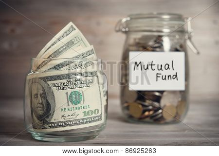 Dollars and coins in glass jar with mutual fund label, financial concept. Vintage tone wooden background with dramatic light.