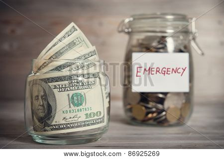 Dollars and coins in glass jar with emergency label, financial concept. Vintage tone wooden background with dramatic light.
