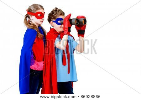 Boy and girl teenagers in a costume of superheroes looking through binoculars. Isolated over white background.