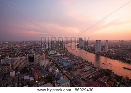 top view bangkok urban view and curve of chaophraya river and sky scrapper in beautiful sun set time