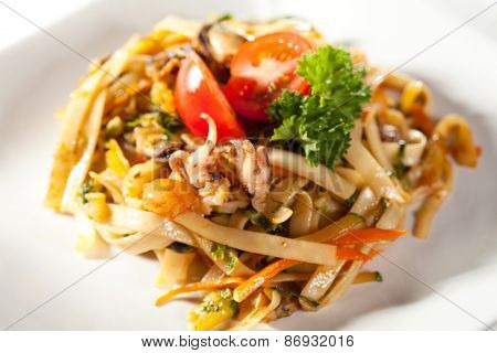 Japanese Cuisine - Udon with Seadood and Vegetables. Garnished with Cherry Tomato and Parsley
