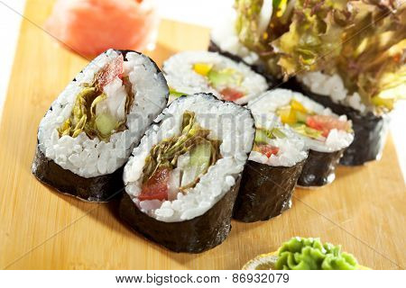 Vegetarian Maki Sushi -  Roll made of Tomato, Cucumber, Bell Pepper, Salad Leaf and Cream Cheese inside. Nori outside
