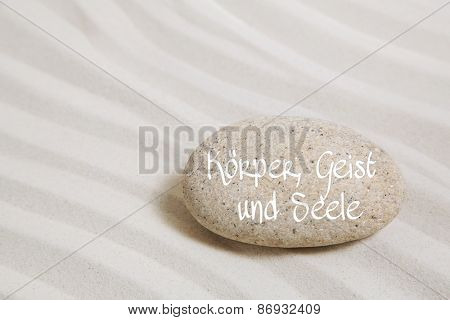 Stone in the sand with german words for body, mind and soul. Background for spa and wellness concepts.