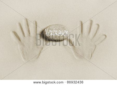Two hands print in the sand with a stone and the word trust in german language.