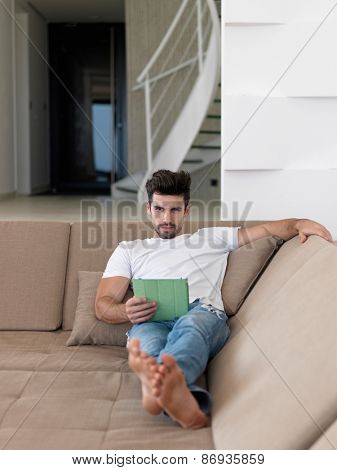 Handsome relaxed young businessman working from home on tablet computer