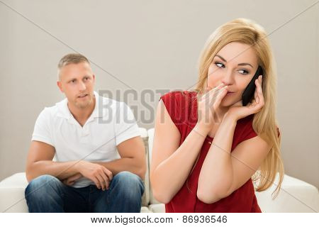 Wife Talking On Mobile Phone While Husband On Sofa