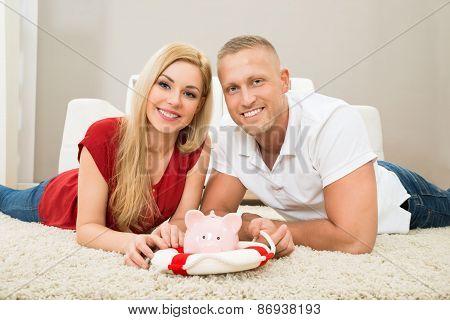 Happy Couple With Piggybank And Lifebuoy