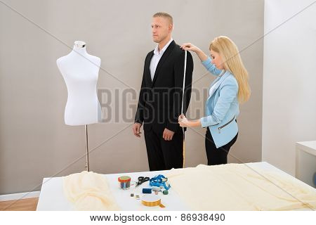 Female Tailor Taking Measurement Of Suit