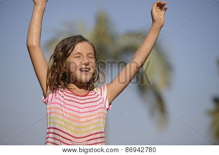 Happy smiling little girl happy outdoor in a sunny day enjoying the light rain.