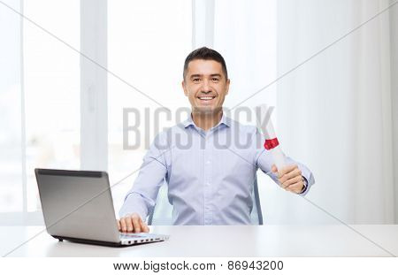 education, graduation, business, technology and people concept - smiling man with diploma and laptop computer sitting at table home or office