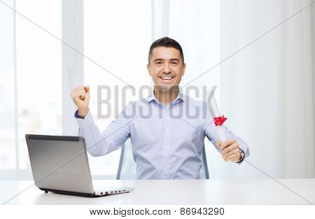education, graduation, business, technology and people concept - smiling man with diploma and laptop computer sitting showing triumph gesture hand