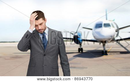 business, crisis, fail, people and travel concept - businessman having headache over airplane on runway background