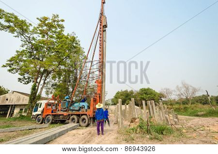 Thai Workers Positioning Pile Driver On A Construction Site