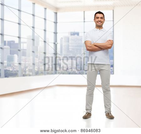 real estate, sale, business and people concept - smiling man with crossed arms over empty apartment or office room with big window and city view background