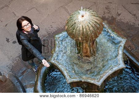 Young woman backpacker tourist in Europe looking the fountain in Barcelona, Spain