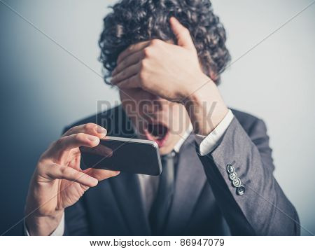 Shocked Businessman Reading On His Smartphone