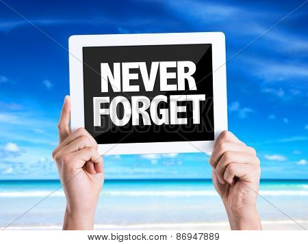 Tablet pc with text Never Forget with beach background