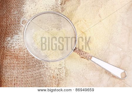Flour with sieve on burlap cloth, closeup
