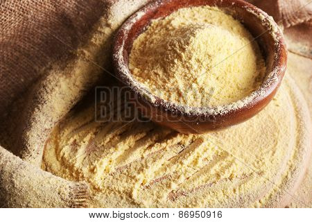Bowl of whole flour on wooden cutting board with burlap cloth, closeup