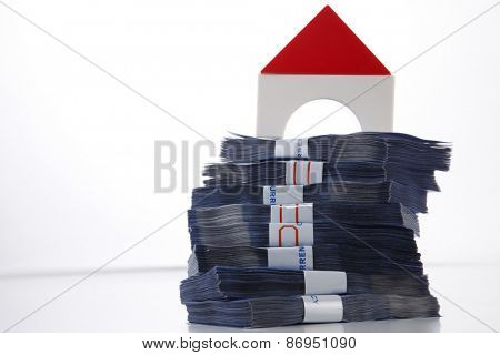 modal house on top of money stacked high