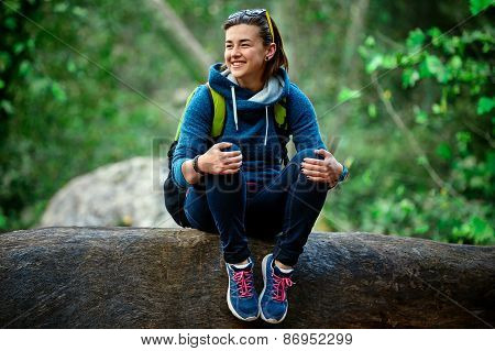 Woman hiker smiling standing outside in forest with backpack
