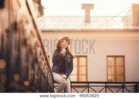 Beautiful Girl Sitting On The Railing Of A Hat