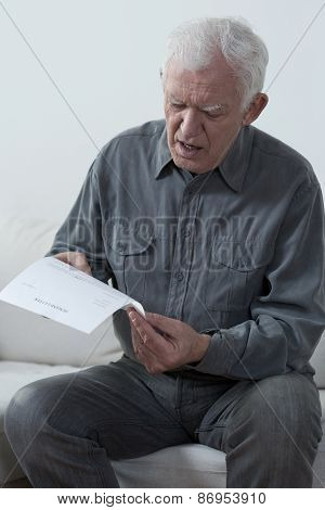 Aged Man Reading Unpaid Bill