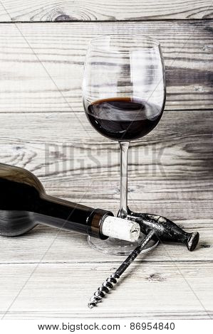 A wine glass, a cork, a corkscrew and a bottle on a wooden background