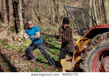 Old Man And A Strong Man Working With A Tractor