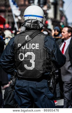 Detail Of The Back Of A Police Facing Protesters.