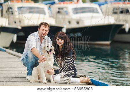 A young couple spends time on the dock in the summer near the yacht club.