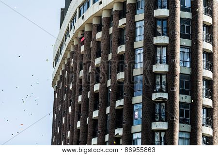 Man Throwing Papers From His Balcony To Encourage The Protesters