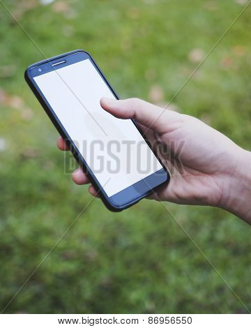 Hand Holding Mobile Smart Phone With Blank Screen With Blurred Outdoor Background