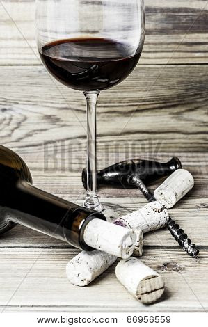 A wine glass, corks, a corkscrew and a bottle on a wooden background