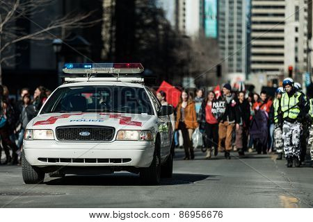 Police Car In Front Of The Protesters Controlling The Traffic