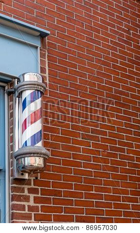 Traditional Barber Pole By Brick Wall