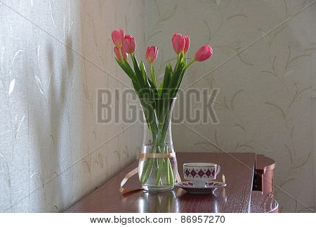 Pink Tulips In A Transparent Vase And A Tea Cup