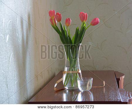 Pink Tulips In A Transparent Vase On A Wooden Dresser