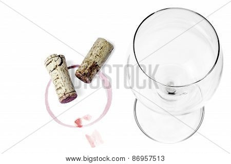 An empty wine glass, a cork and a wine imprint on a white background