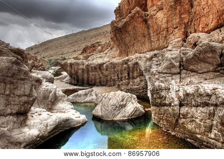 Colorful rocks in a tranquil rock pool in Wadi Bani Khalid near Muscat, Oman