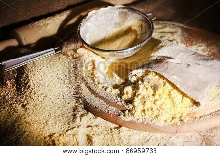 Pile of whole flour in bag with sieve on wooden cutting board, closeup