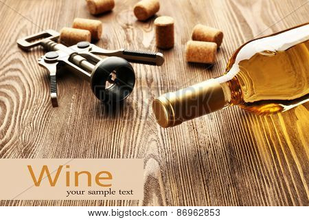 Bottle of wine with corks and corkscrew on wooden table background