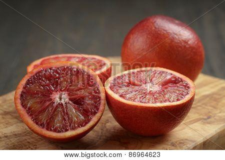 red sicilian oranges sliced on olive board